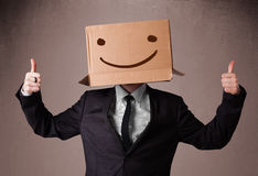 Businessman gesturing with a cardboard box on his head with smil Stock Images