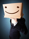 Businessman gesturing with a cardboard box on his head with smil Stock Photo