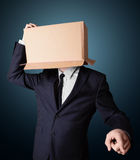 Businessman gesturing with a cardboard box on his head Royalty Free Stock Photography