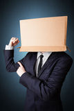 Businessman gesturing with a cardboard box on his head Stock Image
