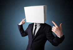 Businessman gesturing with a cardboard box on his head Stock Images