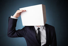 Businessman gesturing with a cardboard box on his head Stock Photo