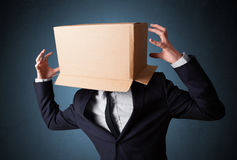 Businessman gesturing with a cardboard box on his head Royalty Free Stock Photos