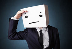 Businessman gesturing with a cardboard box on his head with stra Stock Photography