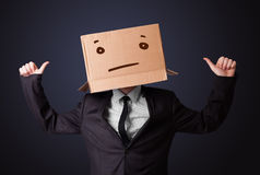 Businessman gesturing with a cardboard box on his head with stra Royalty Free Stock Images