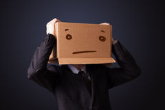 Businessman gesturing with a cardboard box on his head with stra Stock Photos