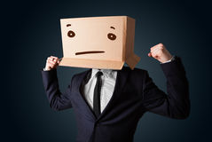 Businessman gesturing with a cardboard box on his head with stra Stock Images