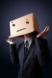 Businessman gesturing with a cardboard box on his head with stra Stock Photo