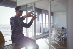 Businessman gesturing while experiencing virtual reality in office Royalty Free Stock Image