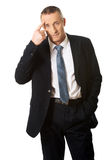 Businessman gesturing with finger against temple Stock Image