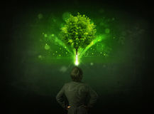 Businessman gesturing in front of a glowing tree Stock Image
