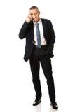 Businessman gesturing idiot sign Stock Photo