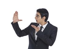 Businessman gesturing and l. Ooking at his hand Stock Photo