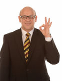 Businessman gesturing OK. Happy middle aged businessman with bald head gesturing OK, white background royalty free stock photo