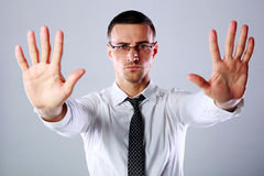 Businessman gesturing stop sign with both hands. Confident businessman gesturing stop sign with both hands on gray background Royalty Free Stock Image