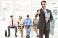 Businessman gesturing thumbs up against people waiting for interview Stock Photos