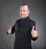Businessman gesturing thumbs up with both hands. Portrait of young businessman gesturing thumbs up with both hands on a gray background stock images