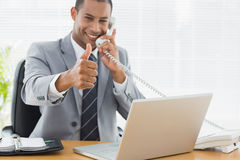 Businessman gesturing thumbs up while on call at desk Royalty Free Stock Photos
