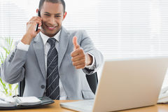 Businessman gesturing thumbs up while on call at office desk Stock Photos