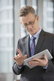 Businessman gesturing while using digital tablet in office Stock Images