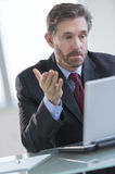 Businessman Gesturing While Using Laptop At Desk Royalty Free Stock Photography