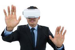 Businessman gesturing while wearing vr glasses. Against white background Royalty Free Stock Image