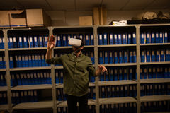 Businessman gesturing while wearing VR glasses in file storage room. At workplace Stock Image