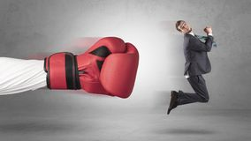 Businessman gets a hit from a giant hand. With boxing gloves Royalty Free Stock Photo