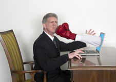 Businessman Gets Surprise Punch From Laptop. Must be a rough day on the internet! A businessman gets a surprise sucker punch as a fist with a boxing glove jumps Royalty Free Stock Photo