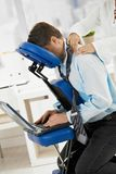 Businessman getting neck massage. Businessman sitting on massage chair, getting back massage