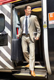 Businessman Getting Off Train At Platform Royalty Free Stock Photos
