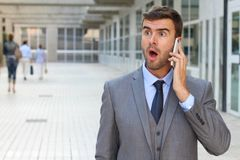 Businessman getting shocking news on the phone Stock Image