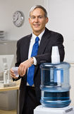 Businessman getting water from water cooler. Businessman getting water from a water cooler Stock Image