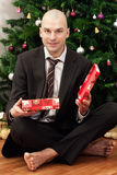 Businessman with a gift under the tree Stock Image