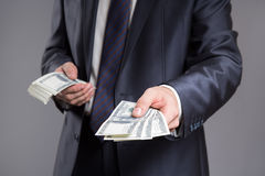 Businessman give dollars. Gray background. Royalty Free Stock Photography