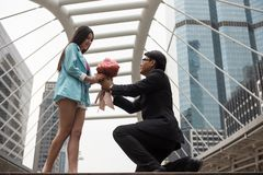 Businessman give flower bouquet to young girlfriend. Senior Businessman give flower bouquet to beautiful young Asian girlfriend in mordern city. Will you marry royalty free stock photos