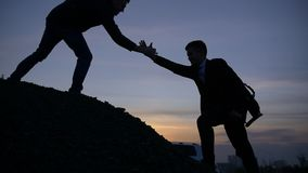 Businessman silhouette gived hand for pull team to peak mountain work together