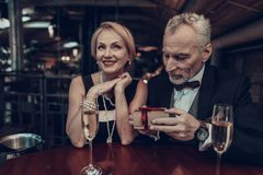 Businessman gives gift to his Woman in Restaurant stock photography