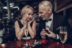 Businessman gives ring to his Woman in Restaurant stock photography