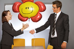 Businessman giving balloon to businesswoman in office Royalty Free Stock Photography