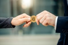 Businessman giving bitcoin to another person. hands exchanging cryptocurrency. Businessman giving golden bitcoin to another man. two hands exchanging stock images