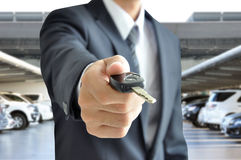 Businessman giving a car key - car sale & rental concept. Businessman hand giving a car key - car sale & rental business concept Royalty Free Stock Images