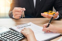 Businessman giving car key and customer signing loan agreement w. Ith calculator on wooden desk stock image