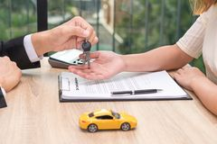 Businessman giving car key over car loan application document wi. Th car toy and calculator on wooden desk royalty free stock photos