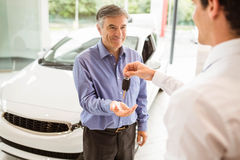 Businessman giving car key to a customer Royalty Free Stock Image
