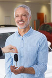 Businessman giving car key to happy customer. At new car showroom Stock Image