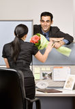 Businessman giving co-worker flowers. Businessman giving his co-worker some flowers Royalty Free Stock Image