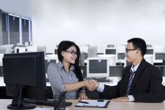 Businessman giving congrats to a new employee. Young businessman giving a congrats sign by shaking hands on new employee with a computer and a document on the royalty free stock photography