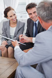 Businessman giving a contract to his partners Stock Images
