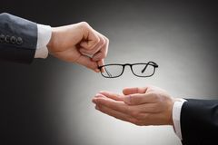 Businessman giving eye glasses to his colleague Stock Image
